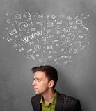 Businessman thinking with social network icons above his head Stock Photography