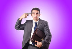 Businessman thinking of suicide against gradient Stock Images