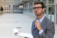 Businessman thinking while taking notes.  Royalty Free Stock Photography