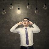 Businessman thinking under light bulb Stock Photo