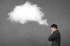 Businessman thinking about white cloud thought bubble with concr Stock Photos