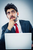 Businessman thinking. Young man working on a laptop focused Stock Photo