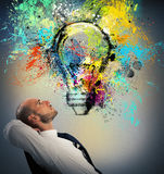 Businessman thinks of a new creative idea. Businessman sitting in a chair watching a light bulb drawn and thinks a new creative idea Stock Photography