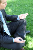 Businessman Thoughts. Young man in business suit and tie sits on green lawn and meditates Royalty Free Stock Photography