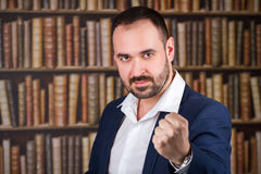 Businessman threatens with a fist in the library Stock Photos