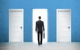 Businessman and three doors. Rear view of a businessman with a suitcase is standing in front of three doors choosing one of them. 3d rendering Stock Image