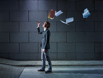 Businessman throwing away files and documents. Young business man walking out from office parking and throwing away paperworks. Horizontal shape, side view, copy Royalty Free Stock Images