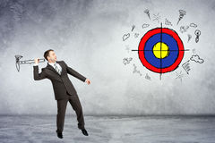 Businessman throwing axe to darts. On grey wall background Stock Photography