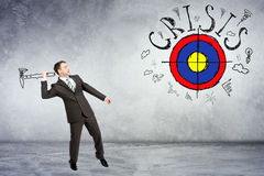 Businessman throwing axe to darts. With word crisis on grey wall background Royalty Free Stock Image