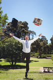 Businessman throwing briefcase and newspaper Stock Photography