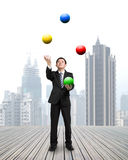 Businessman throwing and catching colorful balls Royalty Free Stock Images