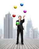 Businessman throwing and catching currency symbol balls. On wooden floor with cityscape background Stock Image
