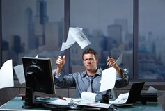 Businessman throwing documents into air. Exhausted businessman throwing documents into air sitting at office desk in overtime royalty free stock photography