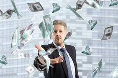 Businessman throwing dollar Stock Images