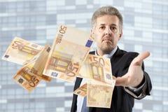 Businessman throwing euro Stock Photo
