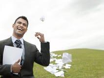 Businessman Throwing Litter On Grass Field Stock Photos