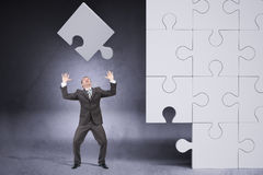Businessman Throwing On Grey Puzzle Piece Stock Photography