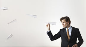 Businessman throwing paper airplanes at target Stock Image