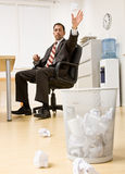 Businessman throwing paper in trash basket Stock Photos