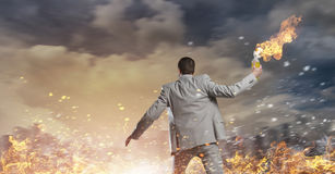 Businessman throwing petrol bomb . Mixed media Stock Photos