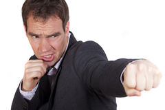 Businessman throwing a punch Royalty Free Stock Photos