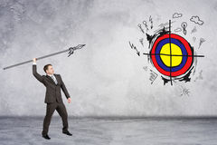Businessman throwing spear to darts. On grey wall background Royalty Free Stock Images