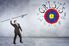 Businessman throwing spear to darts. With word crisis on grey wall background Stock Images