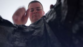 Businessman throws crumpled plastic bottles into the trash. View from inside the basket. Businessman throws crumpled plastic bottles into the trash. View from stock video footage