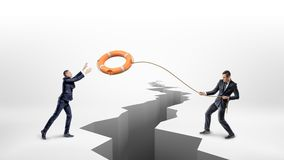 A businessman throws a lifeline with an orange life buoy over a large earthquake crack to another businessman. Royalty Free Stock Photos