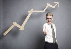 Businessman with thumb up. Concept: Success in business. Confident young businessman holding thumb up in front of ascending business graph, isolated on grey Stock Images