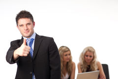 Businessman with thumb up. And colleagues in the background Royalty Free Stock Photo