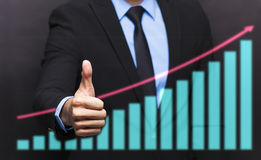 Businessman with thumb up gesture and business graph. Businessman with thumb up gesture and business growing graph concept Stock Images