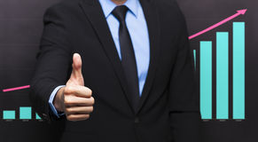 Businessman with thumb up gesture. And business growing graph concept Royalty Free Stock Images