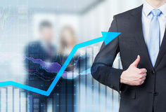 Businessman thumb up and growing arrow. Royalty Free Stock Photo