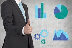 Businessman with thumb up. Businessman showing ok sign and drawing graphs on wall Royalty Free Stock Images