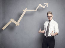 Businessman with thumbs up. Concept: Successful business. Confident young businessman holding thumbs up in front of positiv business graph, isolated on grey Stock Photo