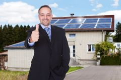 Businessman with thumbs up in front of house stock photo