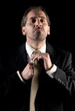 Businessman tie fastening, overwhelmed expression stock photography