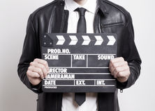 Businessman with tie holding a clapperboard Royalty Free Stock Photos