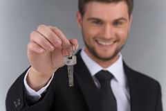 Businessman in tie holding key with focus on key. Stock Photos