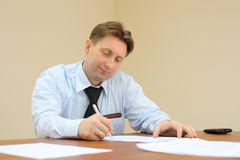Businessman in tie sits at table and signs documents Stock Photography
