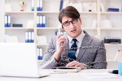 The businessman tied with chains to his work Stock Photo