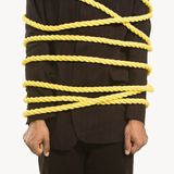 Businessman tied in rope. African American businessman wrapped in yellow rope Stock Photo