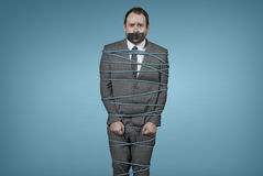 Businessman tied with rope at office Royalty Free Stock Photos