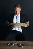 Businessman tied with rope sitting in front of table Stock Photo