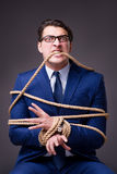 The businessman tied up with rope Stock Photo