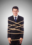 Businessman tied up with rope against gradient Stock Photo
