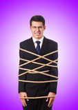 Businessman tied up with rope against gradient Royalty Free Stock Images