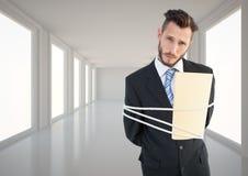 Businessman tied up in rope in corridor. Digital composite image of businessman tied up in rope in corridor Stock Images