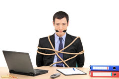 Businessman tied up with rope and gagged with band. A businessman tied up with rope and gagged with band in the office isolated against white background Royalty Free Stock Images